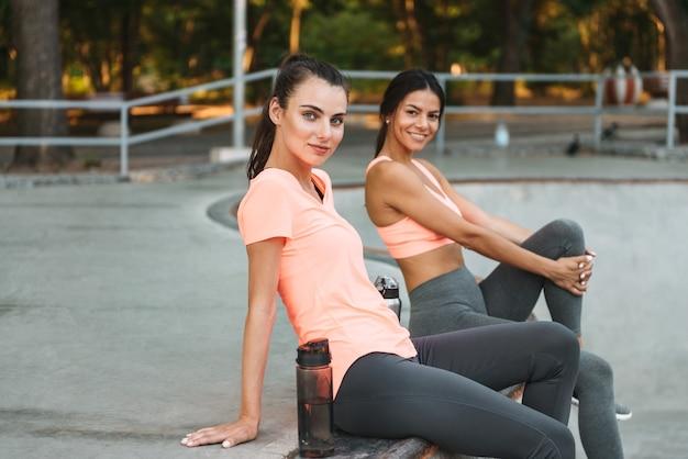 콘크리트 운동장에 물병에 앉아 운동복에 운동 웃는 여성