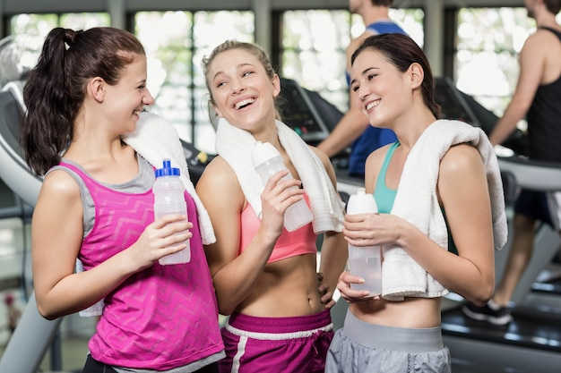 Athletic smiling women posing with bottle of water in gym