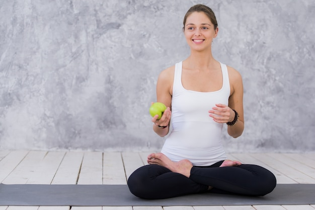 Спортивная (ый) спортивная женщина ест зеленое яблоко после тренировки