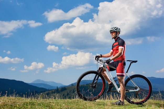 Athletic sportsman cyclist standing with cross country bike on grassy valley, enjoying beautiful view of distant carpathian mountains, summer blue sky with clouds on background. outdoor sport concept