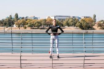 Спортивная спортсменка стоит за перилами у озера