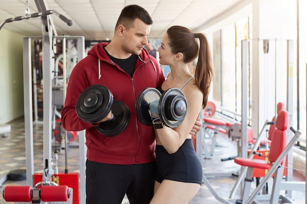 Athletic sporty guy hugs, gives little cuddle to beautiful slim young lady, looks in her eyes attentively. sporty couple holds dumbbills in their hands, sharing time together, wearing sport clothes.