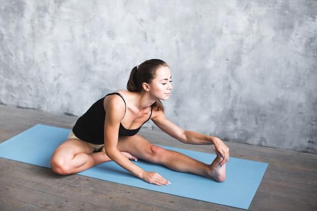 自宅で足を伸ばしてヨガの練習をしている運動スポーティな女性。