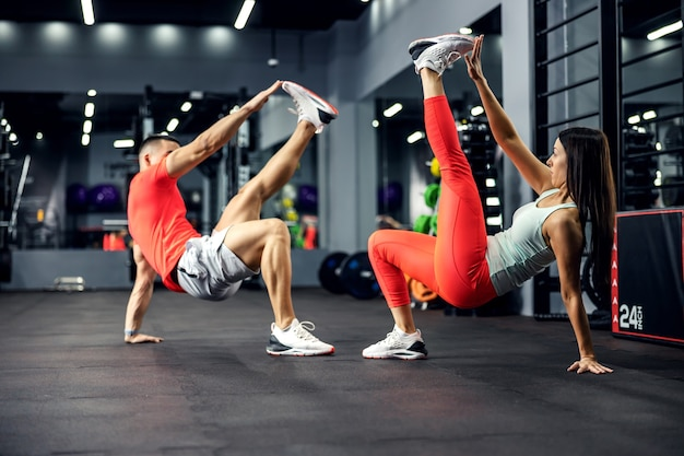 The athletic strong couple performs an acrobatic exercise for the core in the gym with a big mirror and black mat. they stay strong and balanced. relationship fitness goal, sport lover