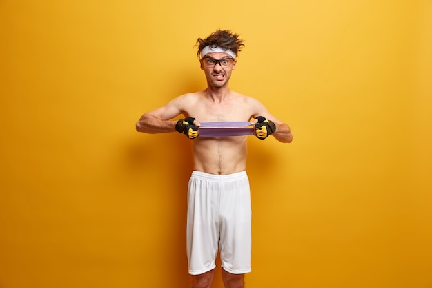 Athletic strong man pulls elastic resistance band, trains hand muscles, has fitness bodybuilding training, wears sport gloves and white shorts, isolated on yellow wall. healthy lifestyle