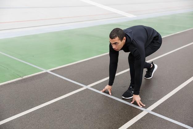 비가 온 후 경기장에서 운동하는 동안 운동을 하는 운동복을 입은 강한 스포츠맨