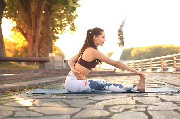 Athletic strong woman practicing difficult yoga pose outdoors.