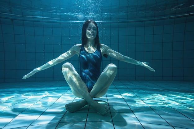 Атлетик пловец улыбается на камеру под водой