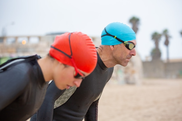 Nuotatori atletici in mute sulla spiaggia