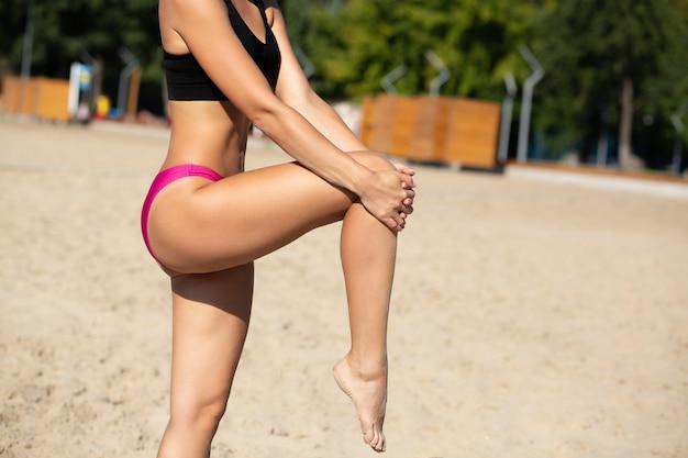 ビーチで足を伸ばしている運動日焼けした女の子。テキスト用のスペース