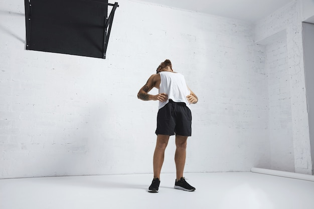 Спортивный татуированный мужчина в белой пустой майке, растягивающий грудь и брюшной пресс после тренировки, изолирован на кирпичной стене, рядом с черной перекладиной