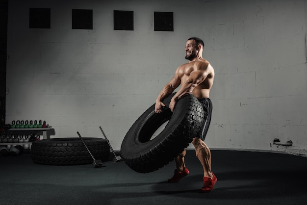 Athletic training muscular man flipping tire at gym