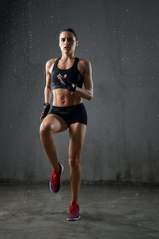 Athletic wet woman jogging on spot