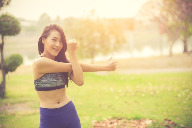 Athletic woman asian warming up and young female athlete sitting on an exercising