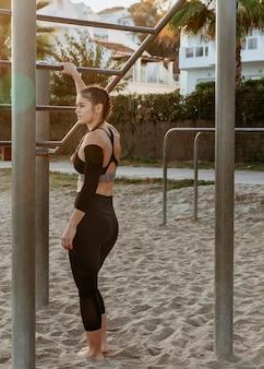 Спортивная (ый) женщина на пляже делает фитнес-упражнения