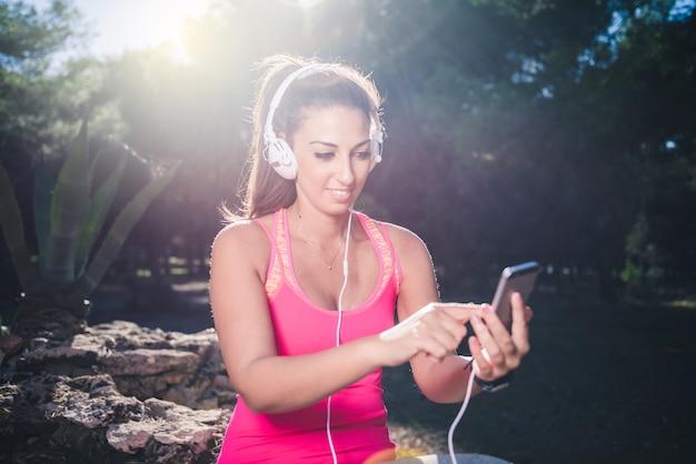 彼女のスマートフォンアプリ、フィットネスの概念を設定して実行を開始する前に運動の女性
