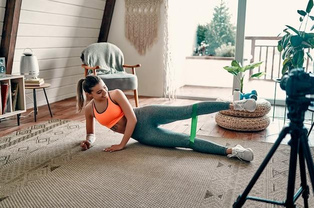 スポーツウェアのアスレチック女性ブロガーは、自宅の居間でゴムバンドを使ってエクササイズをしているときに、カメラでビデオを撮影します。スポーツとレクリエーションのコンセプト。健康的な生活様式。