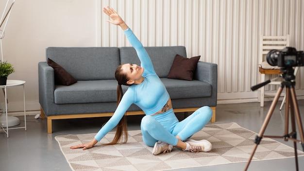 운동복에 운동 여성 블로거는 거실에서 집에서 카메라로 비디오를 촬영합니다. 스포츠 및 레크리에이션 개념. 건강한 생활.