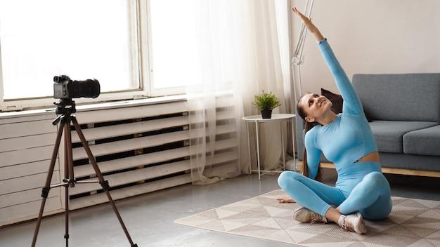スポーツウェアのアスレチック女性ブロガーは、自宅の居間でカメラでビデオを撮影します。スポーツとレクリエーションのコンセプト。健康的な生活様式。