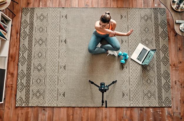 Спортивная женщина-блогер в спортивной одежде сидит на полу с гантелями и ноутбуком и снимает видео на камеру, делая упражнения дома в гостиной. концепция спорта и отдыха. вид сверху.