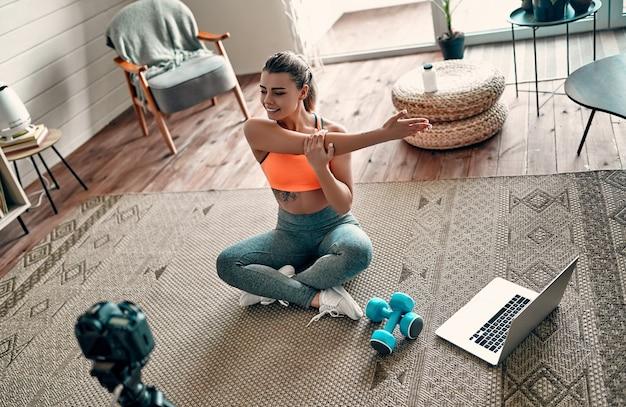 Спортивная женщина-блогер в спортивной одежде сидит на полу с гантелями и ноутбуком и снимает видео на камеру, делая упражнения дома в гостиной. концепция спорта и отдыха.
