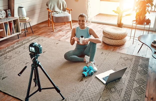 Athletic woman blogger in sportswear sitting on the floor with dumbbells and a laptop and showing a jar of sports nutrition to the camera at home in the living room. sport and recreation concept.