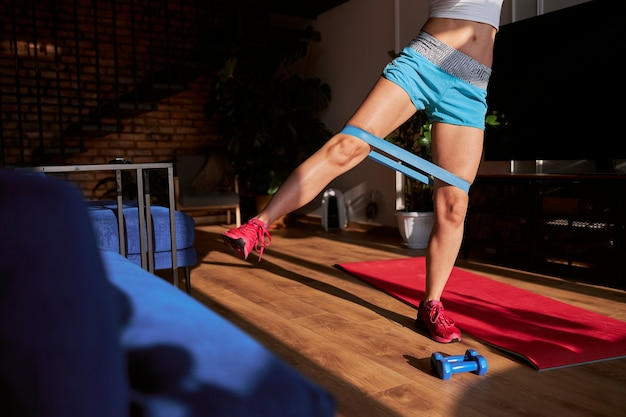 Athletic woman in blue shorts does side leg raising with elastic band at home