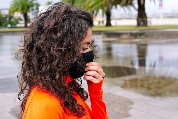 거리에서 마스크와 그녀의 입과 코를 덮고 운동 여자