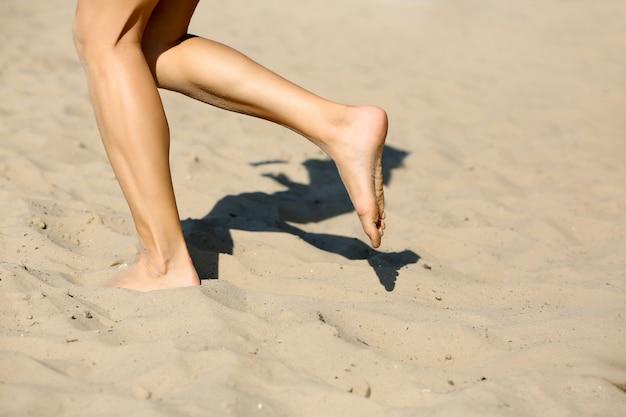 ビーチで有酸素運動をしている運動の女性。彼女の足のクローズアップショット