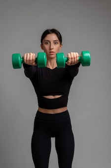 Athletic woman doing dumbbell front raise with both hands on grey surface