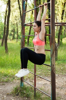 Athletic woman doing exercise for abs in park