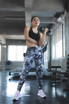 Athletic woman doing exercise for arms and muscular fitness model working out with dumbbells in gym.