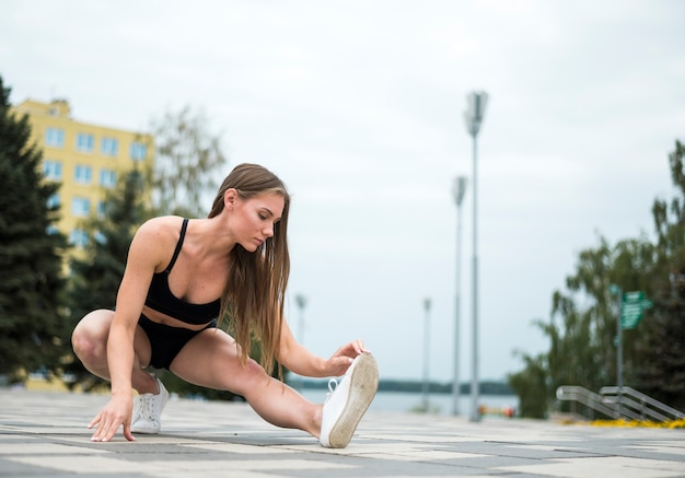 Athletic woman doing exercises  long shot