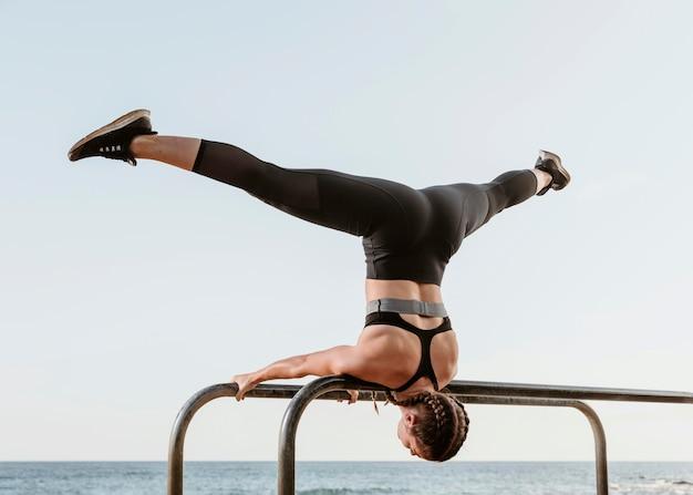 Спортивная (ый) женщина делает упражнения на открытом воздухе на пляже