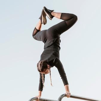 Спортивная (ый) женщина делает упражнения на открытом воздухе