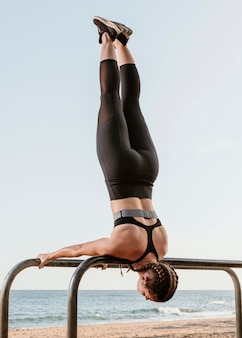 Donna atletica facendo esercizi fuori dalla spiaggia