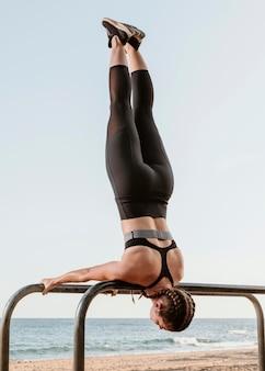 Спортивная (ый) женщина делает упражнения на пляже