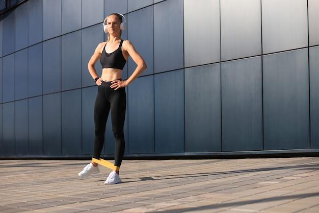 피트니스 껌을 사용하여 피트니스 운동을 하는 운동 여자.