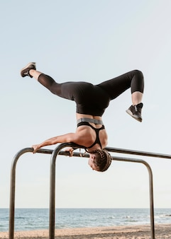 Спортивная (ый) женщина делает фитнес-упражнения на открытом воздухе на пляже