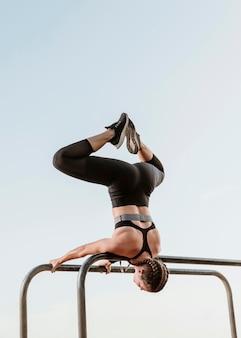 Спортивная (ый) женщина делает фитнес-упражнения на открытом воздухе с копией пространства