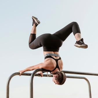 Спортивная (ый) женщина делает фитнес упражнения на открытом воздухе