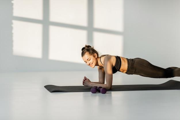 屋内でフィットネスをしている運動の女性