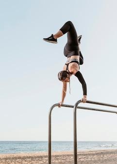 Спортивная (ый) женщина делает фитнес-тренировки на открытом воздухе на пляже