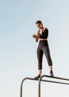 Спортивная (ый) женщина занимается фитнесом на открытом воздухе