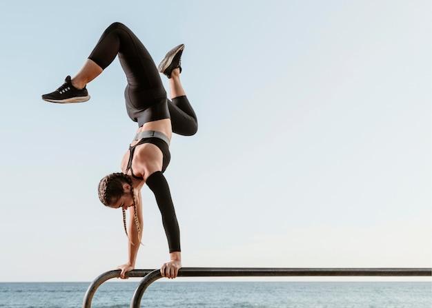 Спортивная (ый) женщина делает фитнес-тренировку снаружи на пляже