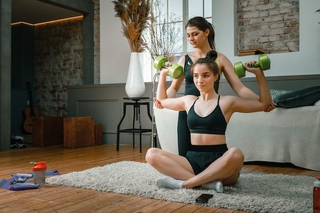 아령으로 손 팔뚝 운동을하는 운동 여성, 두 번째는 침실에서 지원하고 도움이되며 배경에는 침대, 꽃병, 카펫이 있습니다.