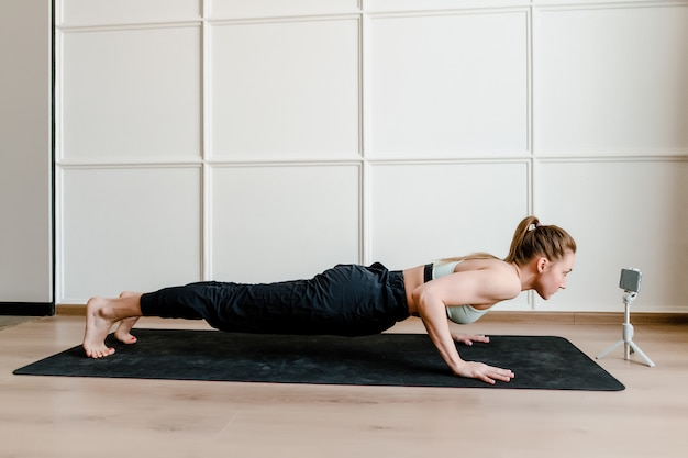 Athletic woman doing physical exercise at home on yoga mat
