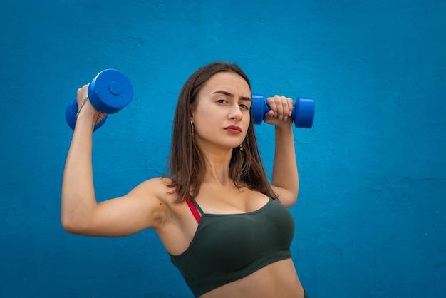 青い背景の上にダンベルを使用して運動をしている運動の女性。スポーツとヘルスケアの概念