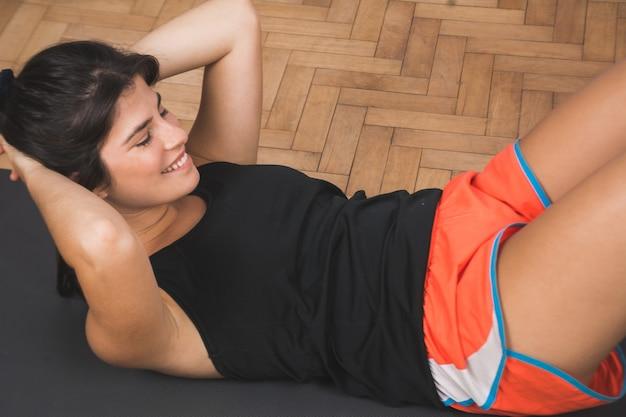 Спортивная (ый) женщина делает упражнения.