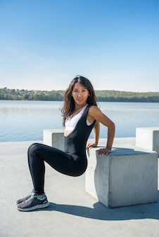 Athletic  woman doing squatting exercise in sunny park near the lake.   concept of wellness and healthy lifestyle